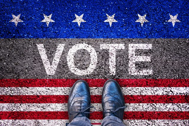 Legs on asphalt road with the word vote, american election concept