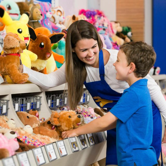 woman smiling at young boy in toy shop