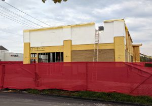 Yellow and white building under construction with red fence