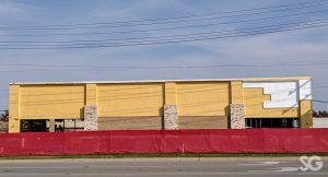 yellow building under construction with a red fence around it