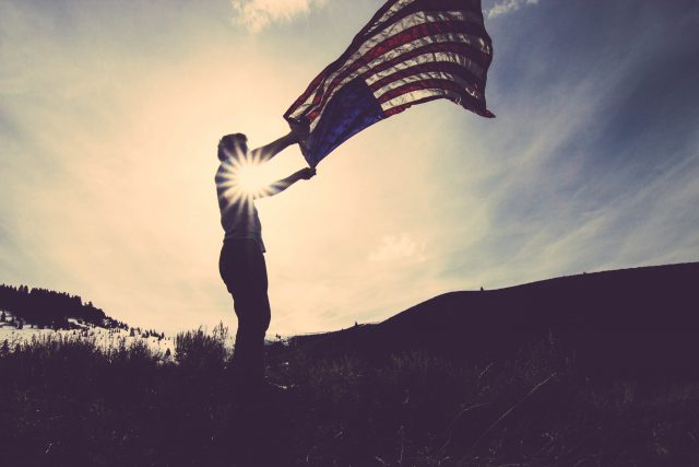 silhouette of someone holding an american flag with the sun on the background
