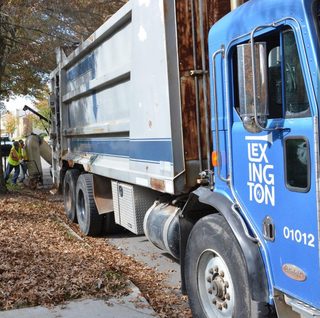 blue and silver garbage truck with lexington in white on the door