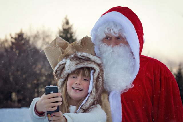 santa claus taking a selfie with a kid outside in the snow