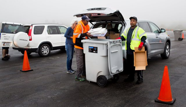 shred event: three men taking paper to be shredded