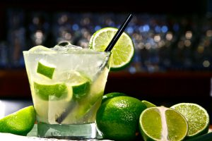 lime margarita with limes surrounding the cup and a blurry bar in the back