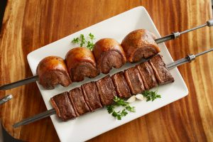 skewer of meats on a white plate with green garnish surrounding it