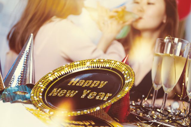 celebrate: a happy new year sign with two girls sipping champagne in the background