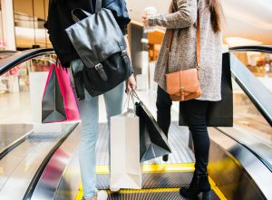 open: two girls with purses and shopping bags going up an escalator