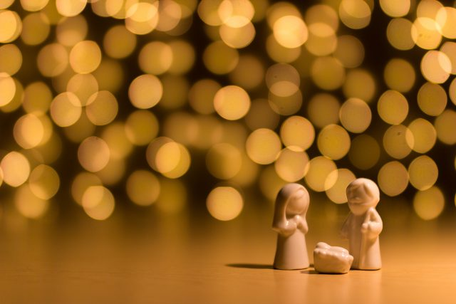 churches: 3 wooden figures to create a nativity scene with white blurry lights in the background