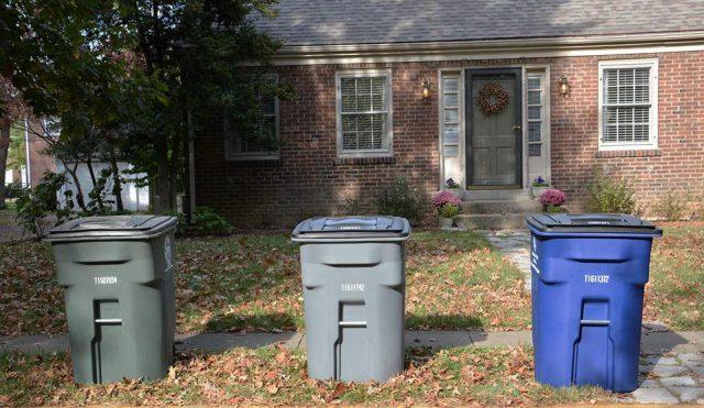 3 trash bins sitting outside of a house