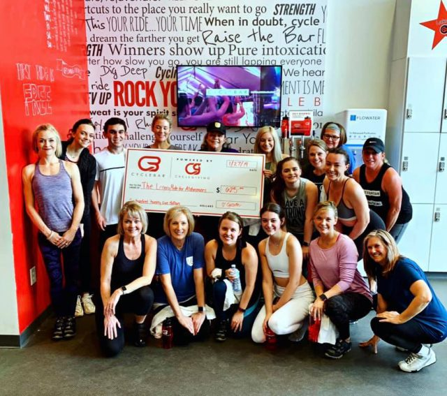group of women posing around a large check for Alzheimer's awareness