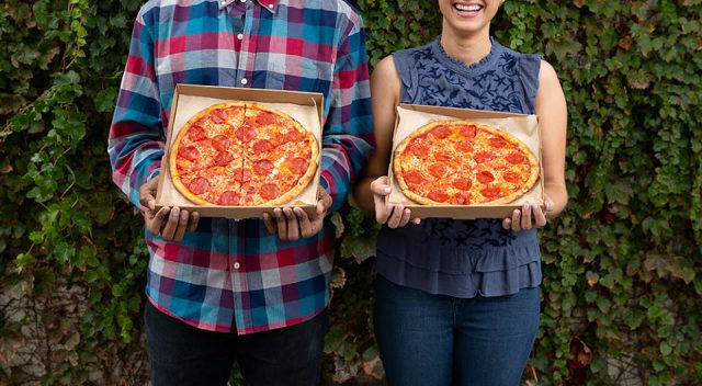 man and woman holding pepperoni pizza in a blaze pizza box