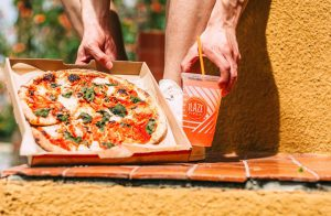 person holding a pizza and drink with blaze pizza on the box and cup