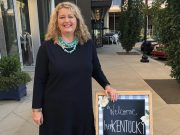 benefiting: a woman in a black dress with a turqoise necklace standing next to a sign that says welcome herkentucky
