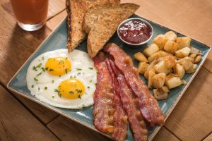 first watch: gray square plate with eggs, bacon, toast, and potatoes with ketchup