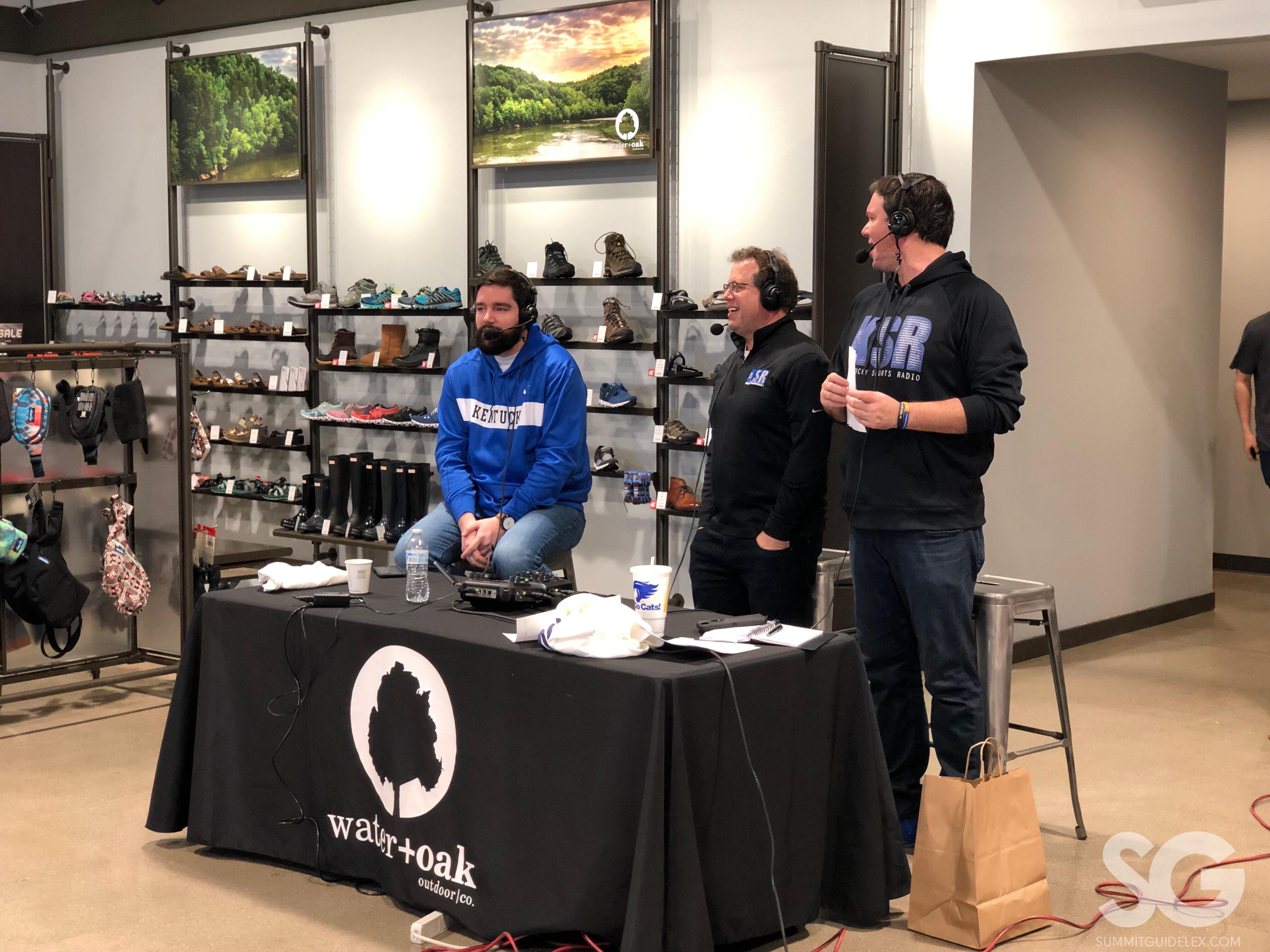 Sports Radio: three guys with headphones on broadcasting a radio show with blue and black sweatshirts