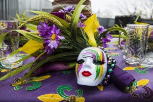 mardi gras mask with purple, yellow, and green and purple flowers