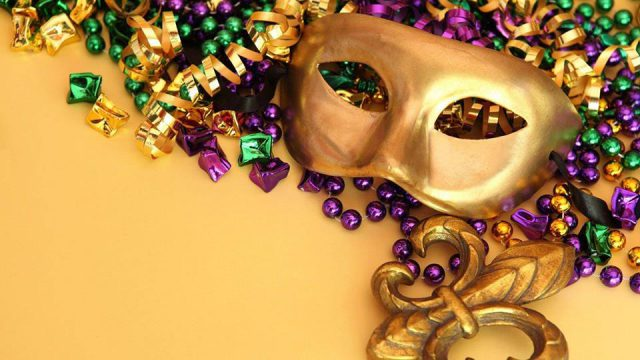 gold mardi gras mask with purple, yellow, and green beads/streamers and a yellow background