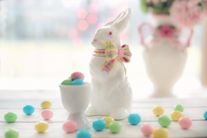 Easter Egg Hunts: small colorful candy eggs in a white porcelin cup and bunny