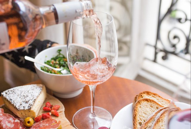 The Summit: Wine being poured into a glass surrounded by food