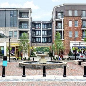 The Henry: apartment complex with retail shops on first floor and a fountain in front