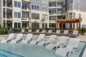 The Henry: lounge chairs in the shallow end of a pool and apartment complex in the background