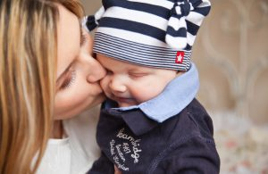 Mother's Day: woman giving her baby boy a kiss on the cheek