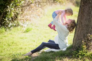 Mother's Day: woman holding her baby over her head leaning against a tree