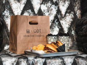 Game of Thrones: a brown bag that says GoT and a burger meal on a tray sitting on a metal chair
