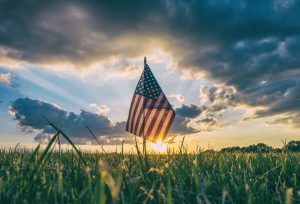 Memorial Day: flag in the grass with a sunset behind