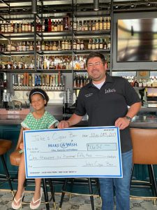 Jake's Cigar Bar: a man and a young girl holding a big check