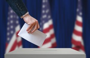 Elections: Election in United States of America. Voter holds envelope in hand above vote ballot. USA flags in background. Democracy concept.