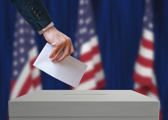 Elections: Primary Election in United States of America. Voter holds envelope in hand above vote ballot. USA flags in background. Democracy concept.