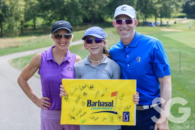 a family holding a yellow flag that says Barbasol and lots of signatures