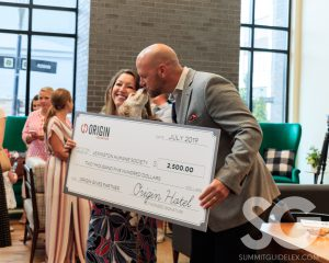 """Origin Hotel: two people holding a big check while a dog """"kisses"""" the man"""