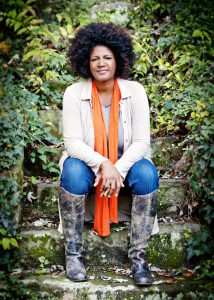 Ouita Michel: woman in a jacket and scarf sitting in nature smiling at the camera