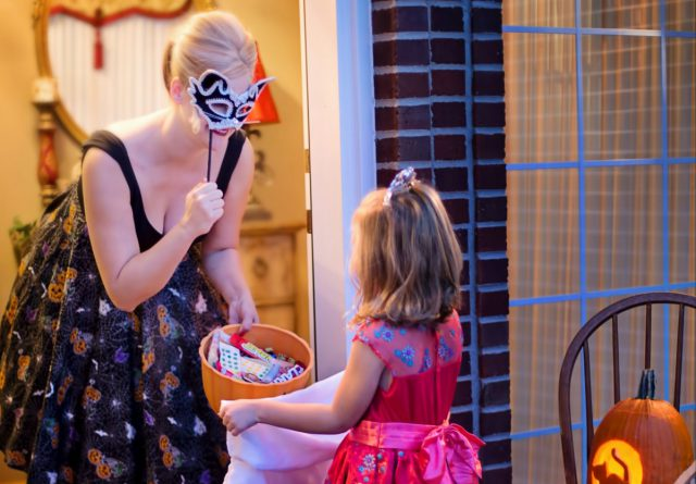 LCA: a woman in a halloween cosutme giving candy to a girl in a halloween costume