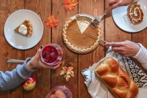 Thanksgiving: table with pumpkin pie, bread, a drink, and hands