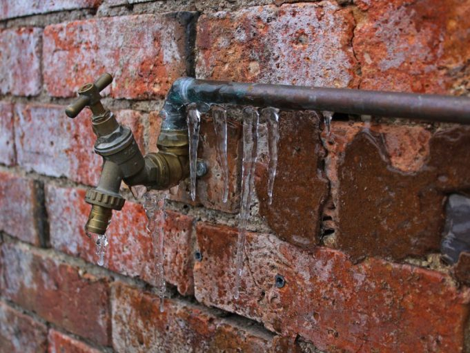 pipes: a pipe with icycles hanging from it against a brick wall